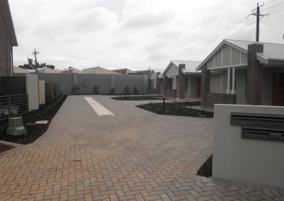 Paved community driveway amongst single storey homes